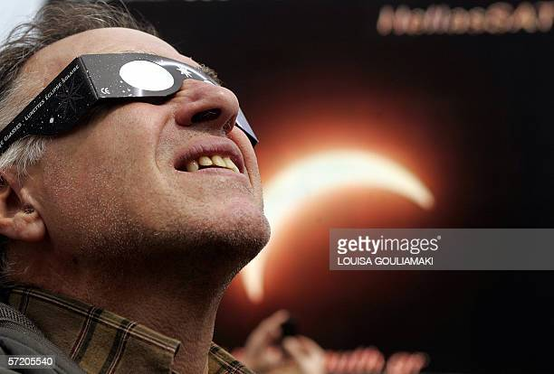 A man looks at the sun through a special glasses at a central Athens square during the partial solar eclipse while a video wall shows the total...