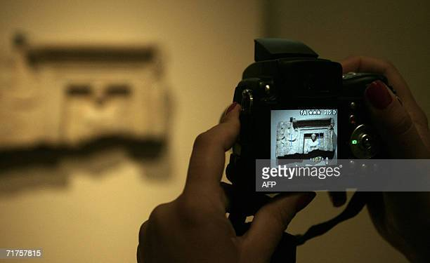 A woman takes a snapshot 31 August 2006 in Athens of an antiquitie dating back to 500bc showing an enthroned goddess in her temple with two...