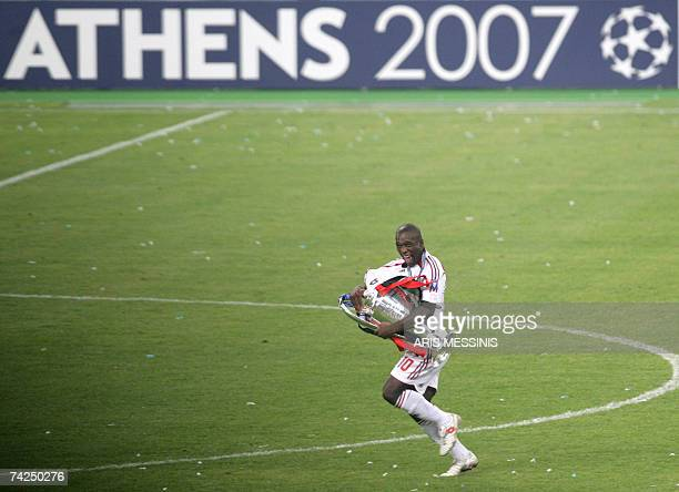 AC Milan's Dutch midfielder Clarence Seedorf runs with the trophy after winning the Champions League final football match at the Olympic Stadium in...