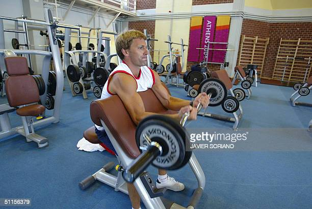 An athlete lifts weights in the fitness room of the Olympic village in Athens 10 August 2004. The Olympic Games start 13 August 2004. AFP PHOTO...