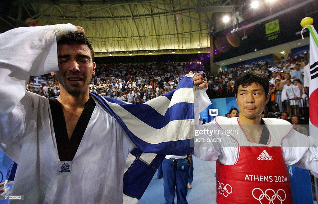 An emotional Alexandros Nikolaidis (L) of Greece reacts following his defeat by Moon Dae-Sung (R) of South Korea in their Olympic Games gold medal +80 kg taekwondo final 29 August 2004 in Athens. Moon knocked out hometown hero Alexandros Nikolaidis, topping off South Korea's gold medal campaign in their own sport at a modest two. AFP PHOTO / Joel SAGET