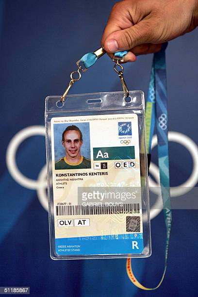 An Olympic Games volunteer holds up the accreditation pass belonging to Greek sprinter Kostadinos Kenteris the 200m gold medalist at the 2000 Sydney...