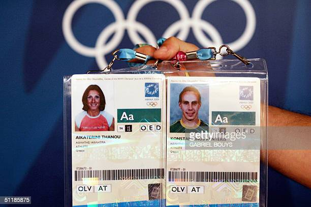 An Olympic Games volunteer holds up the accreditation passes belonging to Greek sprinter Kostadinos Kenteris the 200m gold medalist at the 2000...
