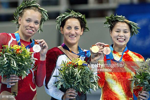 Anna Dogonadze of Germany winner of the women's trampoline final shows her gold medal with silver medallist Karen Cockburn of Canada and bronze...