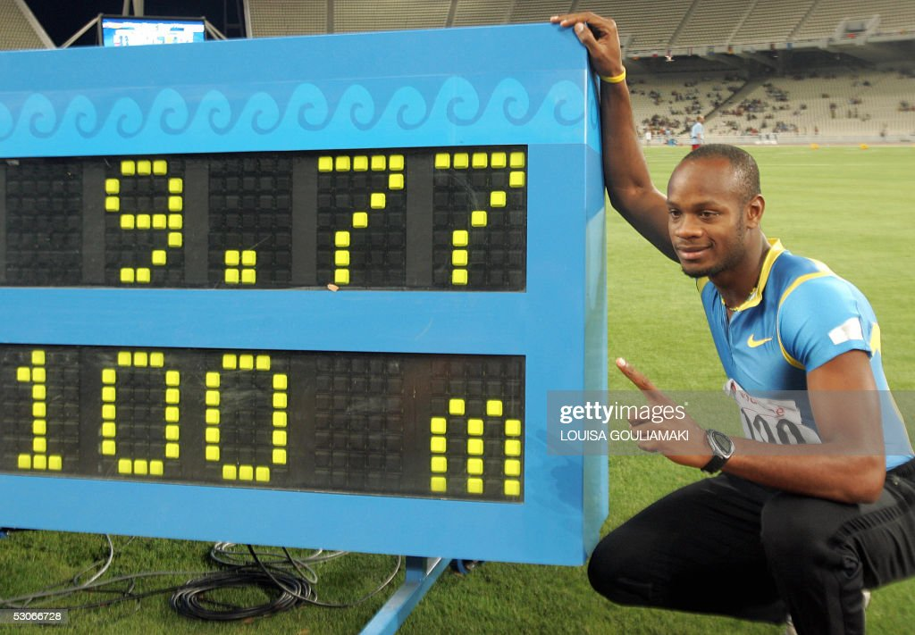 Asafa Powell of Jamaica shows the scoreboard with his world record of 9.77 sec in men's 100m Ghana during the Athens Super Grand Prix Tsiklitira 2005, at the Olympic Stadium in Athens, 14 June 2005. AFP PHOTO Louisa Gouliamaki