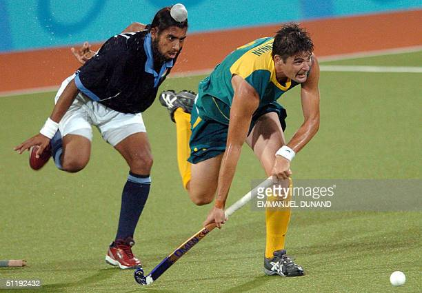 Australian hockey player Michael Brennan aims a shot after having pass India's Harpal Singh during a pool B match of the men's hockey competition at...