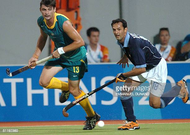 Australian hockey player Michael Brennan and India's Viren Rasquinha eye the ball during a pool B match of the men's hockey competition at the 2004...
