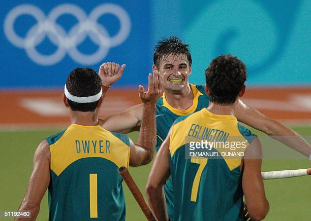Australian hockey player Michael Brennan celebrates with teammates after scoring the winning goal against India during a pool B match of the men's...