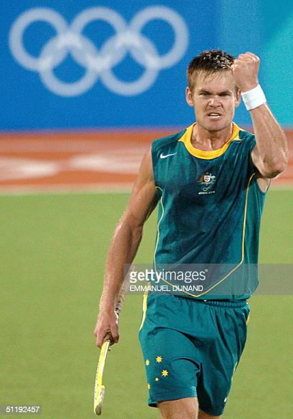 Australian hockey player Michael McCann celebrates after scoring a goal against India during a pool B match of the men's hockey competition at the...