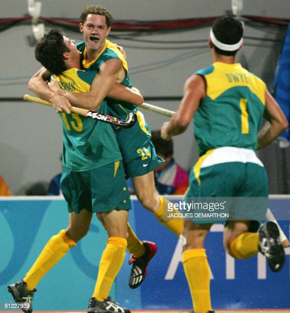 Australia's Travis Brooks celebrates with teammates Michael Brennan and Jamie Dwyer after scoring the first goal 27 August 2004 in Athens during the...