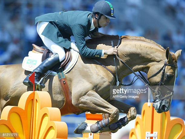 "Brazilian jumping rider Rodrigo Pessoa clears a fence on his horse ""Baloubet Du Rouet"" 24 August 2004 at the Markopoulo Olympic Equestrian Centre in..."