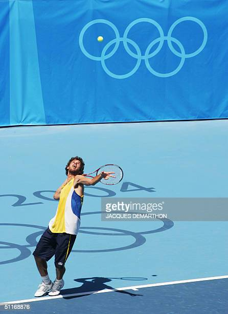 Brazil's Gustavo Kuerten serves during a training session at the Olympic tennis centre 14 August 2004 in Athens, one day before the first match at...