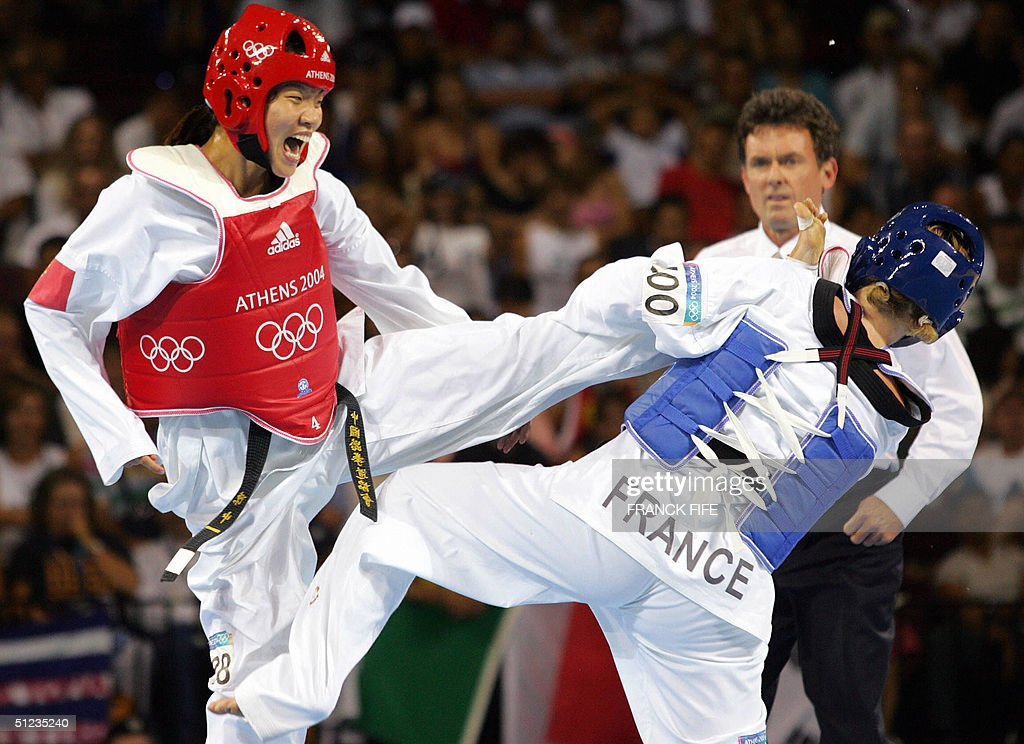 Chen Zhong (L) of China connects against Myriam Baverel (R) of France during their gold medal +67 kg taekwondo final at the Olympics Games 19 August 2004 in Athens. Chen retained her title beating Baverel 12-5. AFP PHOTO / Franck FIFE