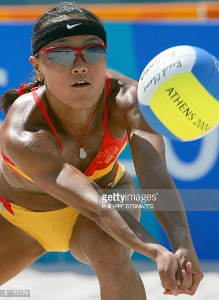 China's Fei Wang returns the ball with partner Jia Tian during the second round beach volleyball match at the 2004 Olympic Games in Athens 16 August...