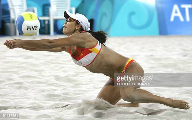 China's Jia Tian returns the ball as team mate Fei Wang plays at her side during the third round beach volleyball match at the 2004 Olympic Games, in...