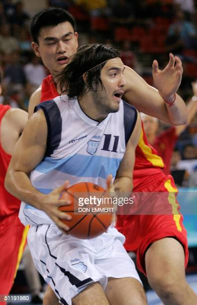 China's Yao Ming guards Argentina's Luis Alberto Scola 19 August 2004 during the Olympic Games Men's Basketball preliminaries at Helliniko indoor...