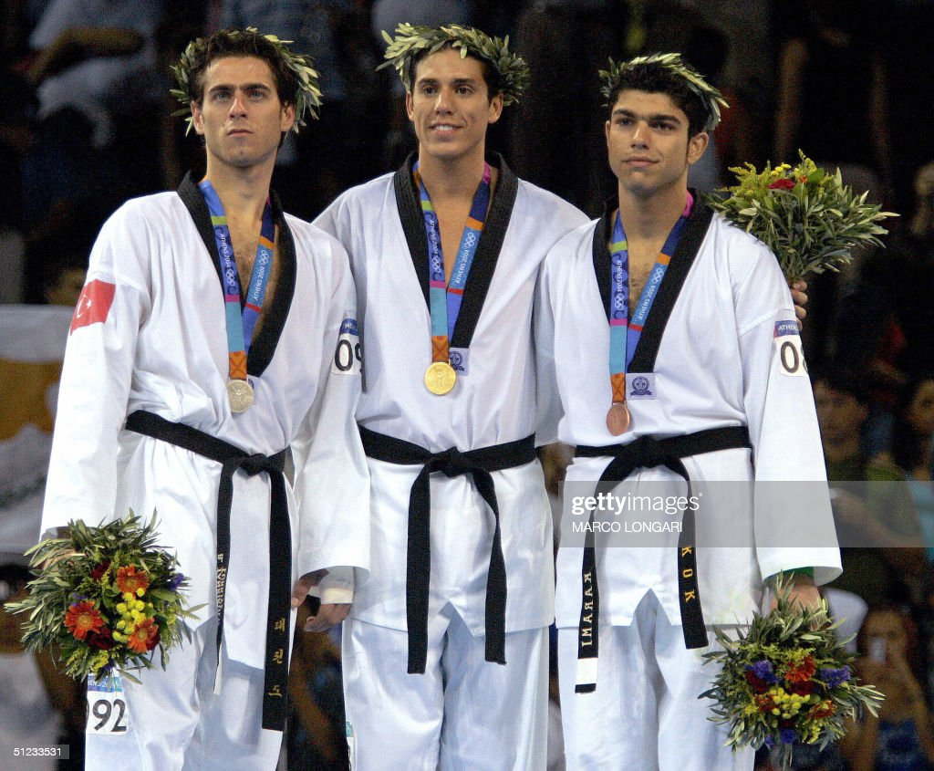 Steven Lopez (C) of the US, gold, Bahri Tanrikulu (L) of Turkey, silver, and Yossef Karami from Iran, bronze pose on the podium after winning the men's under 80kg taekwondo finals at the 2004 Olympic Games in Athens, 28 August 2004.