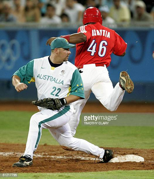 Cuba' Osmani Urrutia is safe at first after the throw gets by Australia's Brendan Kingman in the fourth inning during their gold medal Olympic Games...