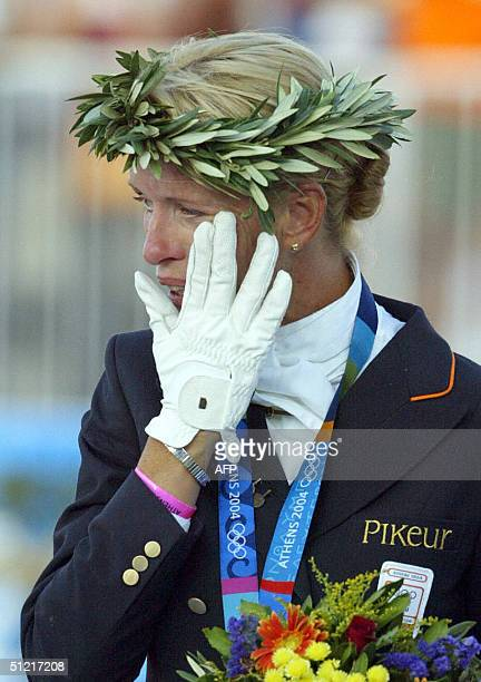 Dutch dressage rider Anky van Grunsven wipes a tear of joy during the medal ceremony 25 August 2004 at the Markopoulo Olympic Equestrian Centre in...