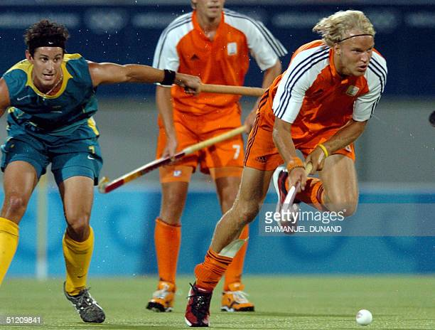 Dutch hockey player Floris Evers drives the ball past Australia's Nathan Elington in their last pool B match of the men's hockey competition at the...