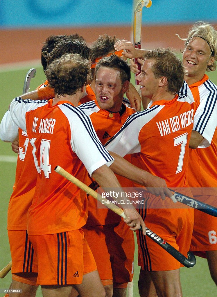 Dutch hockey player Teake Taekema (C) is congratulated by teammates after scoring his team's third goal against India during their match in the first round of the men's hockey competition at the 2004 Olympic Games in Athens, 15 August 2004. Netherlands won India 3-1.