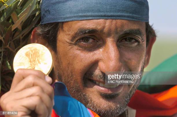 Emirati Sheikh Ahmed AlMaktoum shows his Olympic Games gold medal which he won in the men's double trap final 17 August 2004 at the Markopoulo...