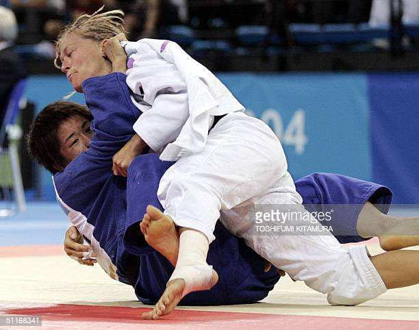 French jukoka Frederique Jossinet pushes Gao Feng of China down during their quarterfinal match in women's under 48kgs category in the judo...