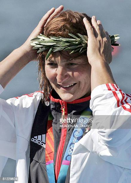 German Birgit Fischer adjusts her wreath after receiving silver medals in Women's K2 500m final for the Athens 2004 Olympic Games at the Schinias...