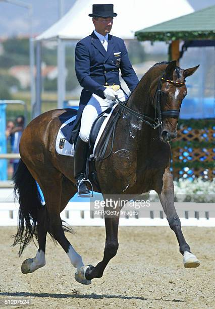 "German dressage rider Martin Schaudt performs on his horse ""Weltall"" , 23 August 2004 at the Markopoulo Olympic Equestrian Centre in Athens during..."