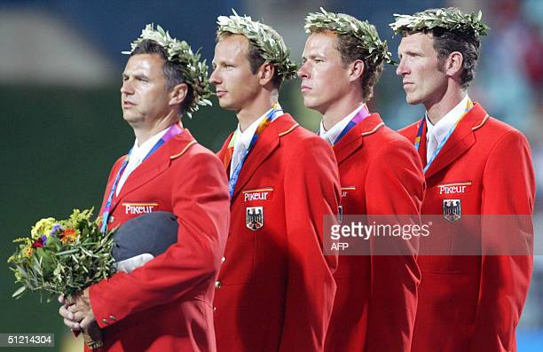 German jumping riders Otto Becker, Marco Kutscher, Christian Ahlmann and Ludger Beerbaum stand on the podium during medal ceremony 24 August 2004 at...
