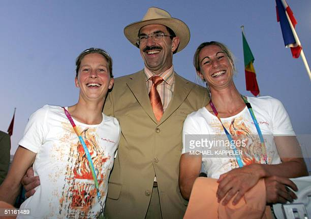German National Olympic Committee head Klaus Steinbach poses with athletes Marion Rodewald and Heike Laetzsch at the Olympic village in Athens, 11...