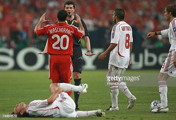 German referee Herbert Fandel speaks to Liverpool's Argentinian midfielder Javier Mascherano as AC Milan's midfielder Gennaro Gattuso looks on during...