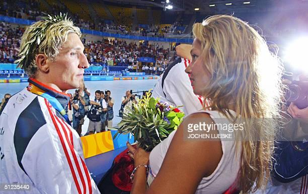 Germany's Stefan Kretzschmar is comforted by his girlfriend German swimmer Franziska van Almsick after the handball gold medal match Croatia vs...