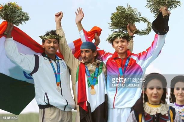 Gold medalist Sheikh Ahmed AlMaktoum of the UAE poses on the winner's podium with silver medalist Indian Rajyavardhan Rathore and bronze medalist...