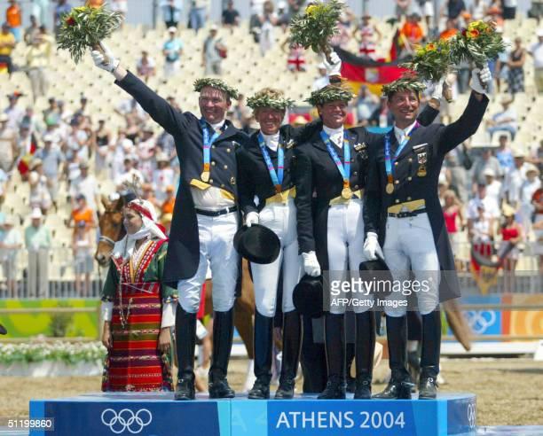 Gold medalists German dressage team Hubertus Schmidt, Heike Kemmer, Ulla Salzgeber und Martin Schaudt wave, standing on the podium 21 August 2004 at...