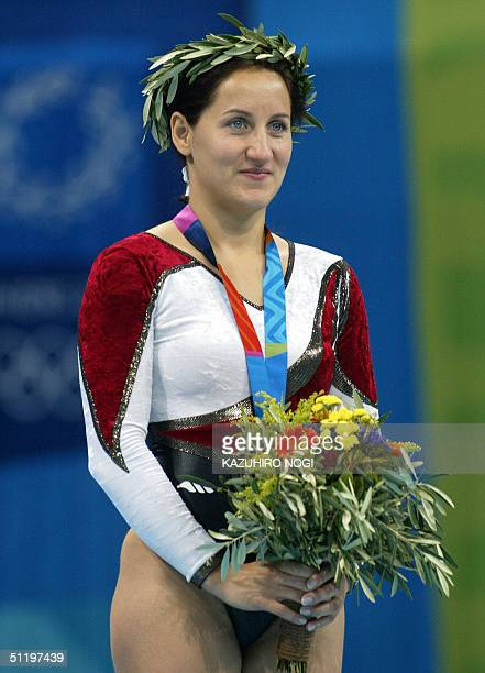 Gold medallist Anna Dogonadze of Germany listens to her national anthem during the awards ceremony for the women's trampoline final 20 August 2004 at...