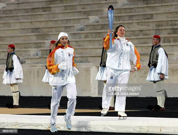 Greek athlete Anna Hadziathanassiou skates holding the torch for the Torino 2006 Winter Olympic Games while Fani Halkia Olympic gold medallist in the...