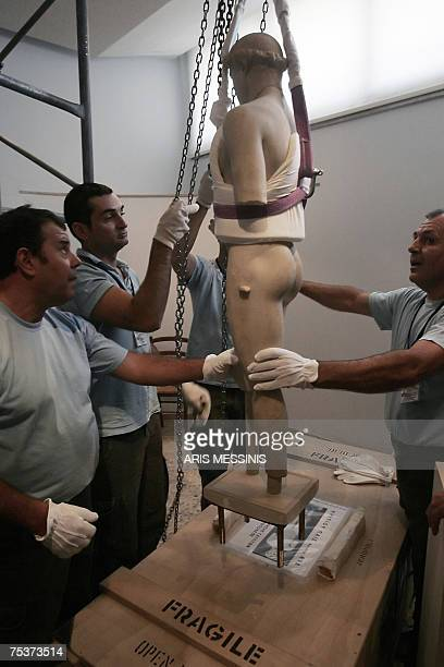 Greek culture ministry workmen place the 5th century BC statue of a youth the 'Kritos boy' into a crate for transportation from the Athens Acropolis...