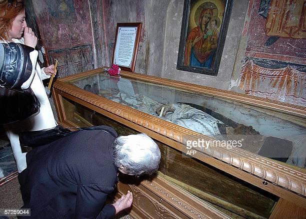 Greek Orthodox believers pray 01 April 2006 in front of a glass case containing the body of monk Vissarionas Korkoliakos at Agathonos Monastery near...