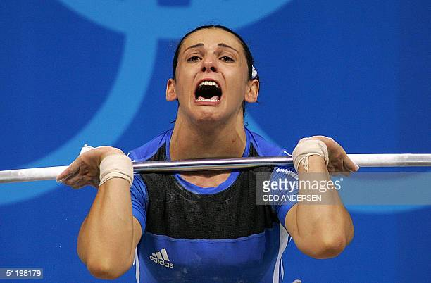 Greek weightlifter and 5th placed Christina Ioannidi attempts to lift 1475 kg in the clean jerk of the women's 75 kg weightlifting 20 August 2004 at...