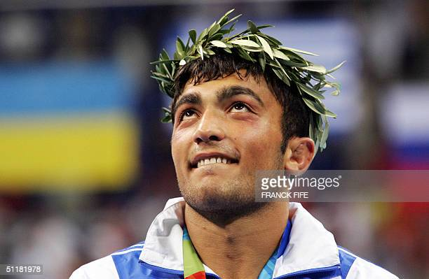 Ilias Iliadis of Greece stands victorious with the laurel wreath after wiining the gold medal in the final of the men's 81 kg Olympic Games...