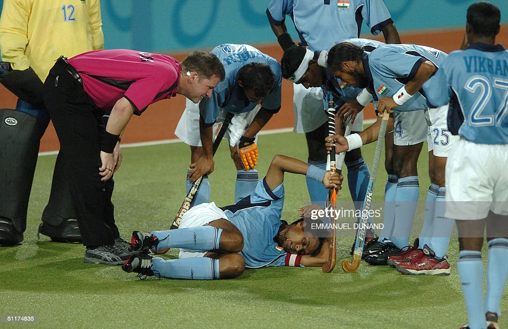 Indian captain Dilip Tirkey (C) lies injured on the ground surrounded by his teammates and umpire after being hit in the head by a ball on a Dutch penalty corner during their match in the first round of the men's hockey competition at the 2004 Olympic Games in Athens, 15 August 2004. The Netherlands won 3-1.