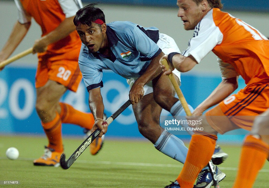 Indian hockey player Gangan Ajit Singh (C) shoots a ball past the Netherlands' Marten Eikelboom during their match in the first round of the men's hockey competition at the 2004 Olympic Games in Athens, 15 August 2004. The Netherlands won 3-1, with Singh scoring the only Indian goal.