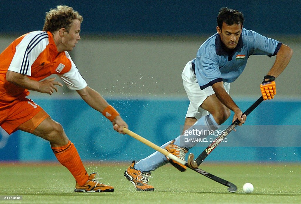 Indian hockey player Viren Rasquinha (R) is challenged by Dutch Marten Eikelboom during their match in the first round of the men's hockey competition at the 2004 Olympic Games in Athens, 15 August 2004. The Netherlands won 3-1.