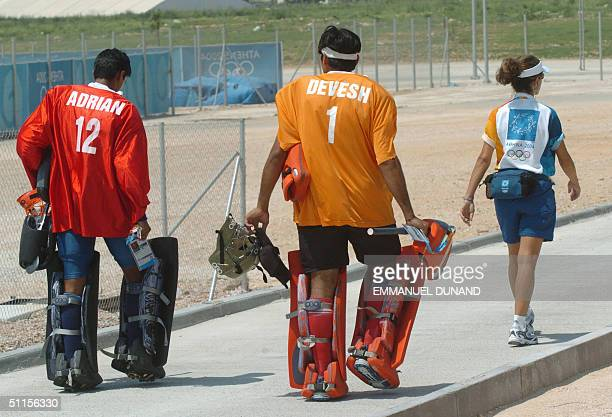 Indian men hockey team goalkeeper Adrian D'Souza and Devesh Chauhan are lead by an International Olympic Committee volunteer to a training pitch...