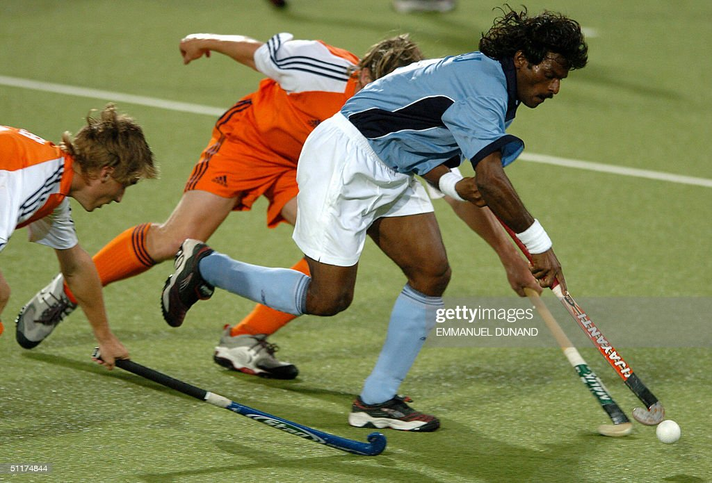 Indian star hockey player Dhanraj Pillay (R) dribbles past two Dutch defenders during their match in the first round of the men's hockey competition at the 2004 Olympic Games in Athens, 15 August 2004. The Netherlands won 3-1.