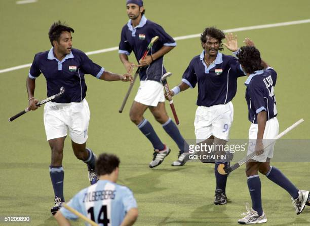 India's Gagan Ajit Singh celebrates after scoring his team's second goal against Argentina during the Olympic Games hockey competition in Athens 23...