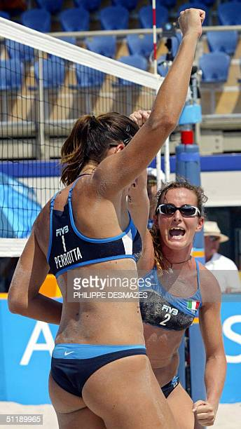 Italy's Lucilla Perrotta and partner Daniela Gatteli celebrate in their third round preliminary women's beach volleyball match at the 2004 Olympic...