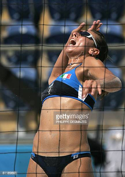 Italy's Lucilla Perrotta reaches up for a smash during her third round preliminary women's beach volleyball match at the 2004 Olympic Games in...