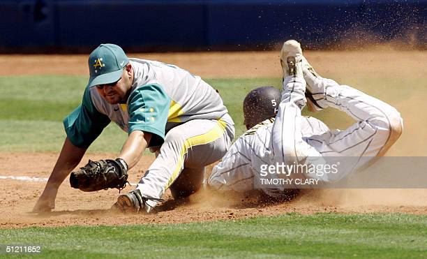 Japan's Norihiro Nakamura slides into first base in a attempt to beat the tag by Australia's Brendan Kingman in the 9th inning of their semifinal 24...